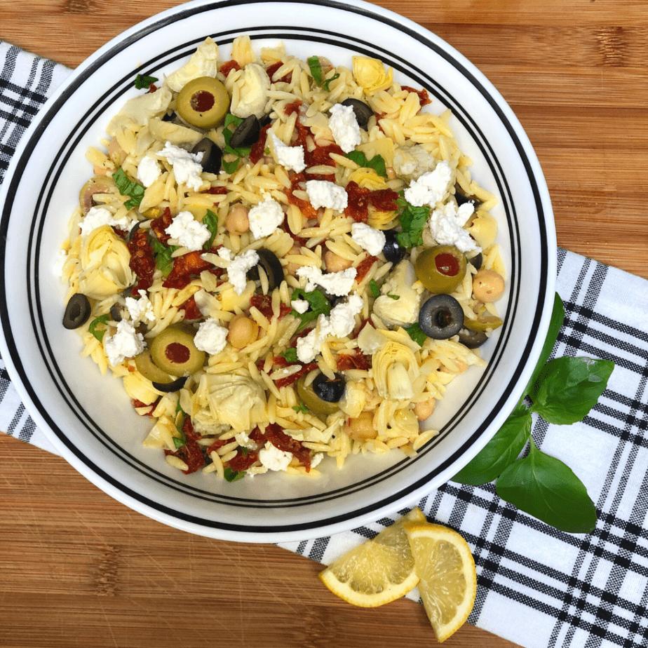 a bowl with vegan lemon artichoke orzo salad