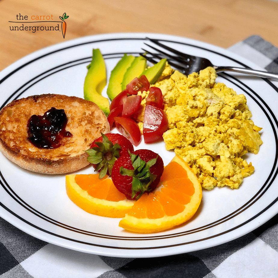 A plate with scramble, orange slices, strawberries, English muffin, avocado slices and tomatoes