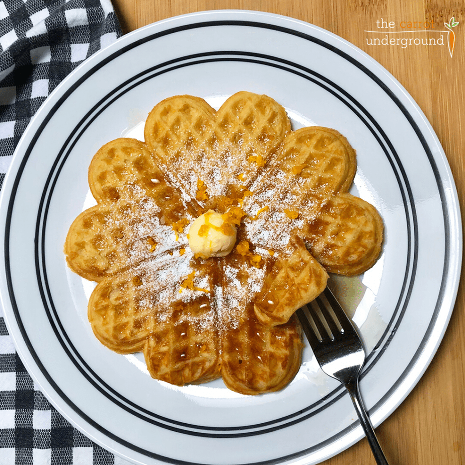 Vegan heart-shaped waffles on a plate with maple syrup and orange zest.