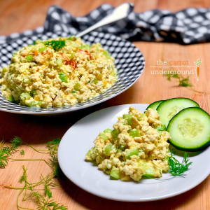 Vegan eggless egg salad in a serving bowl and on a plate with cucumber slices.