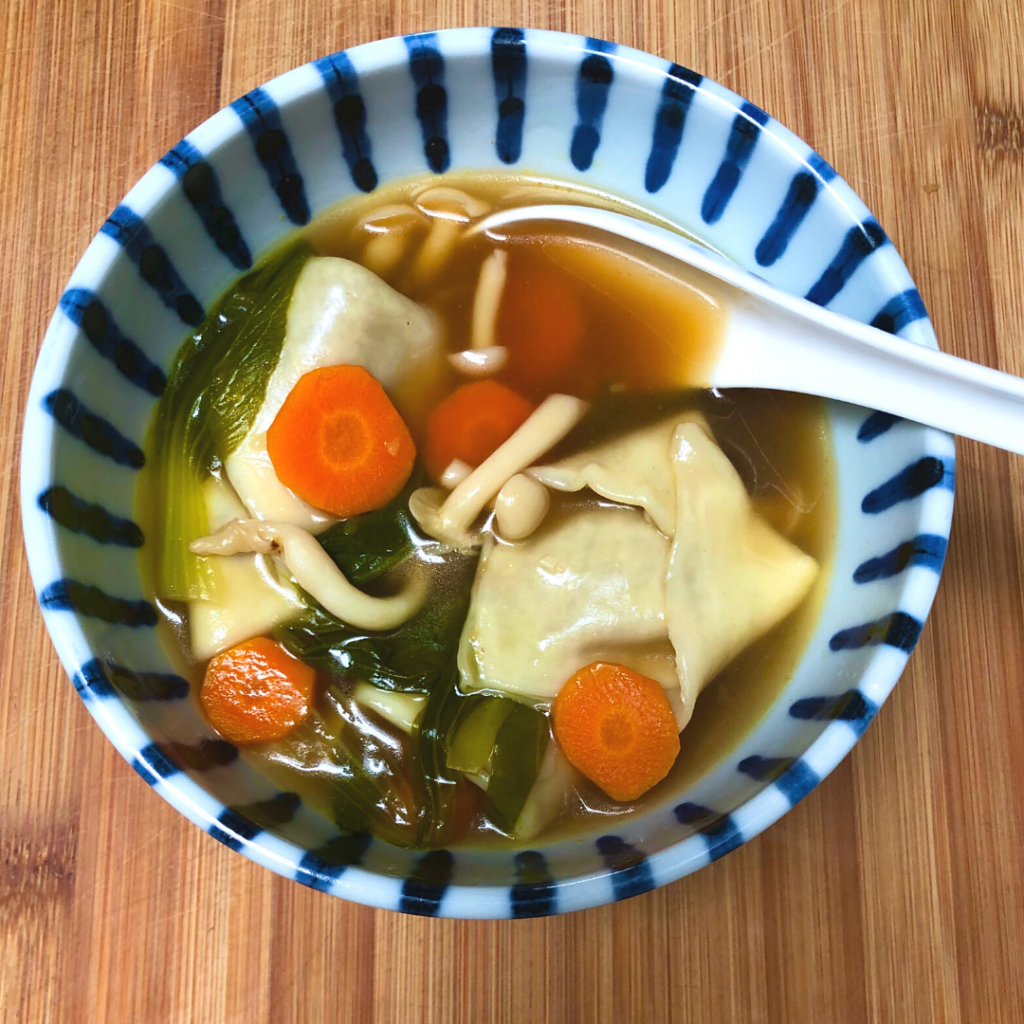 A bowl of vegan wonton soup with carrots and bokchoy.