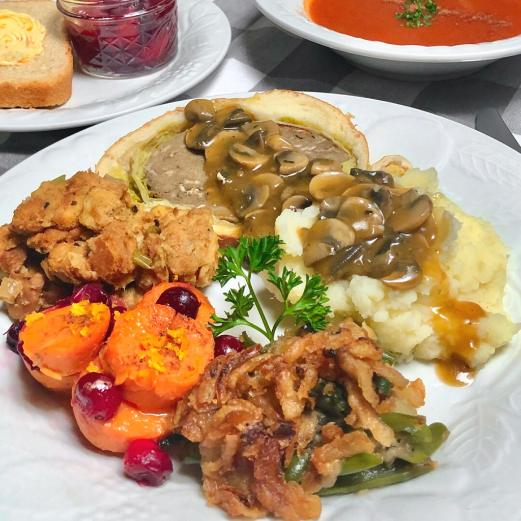 A white dinner plate with a vegan Thanksgiving meal of mushroom seitan Wellington, mashed potatoes and mushroom gravy, bread stuffing, maple cranberry yams and green bean casserole.