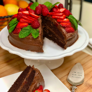 A double layer vegan devil's food cake iced in vegan fudge frosting and decorated with strawberries.