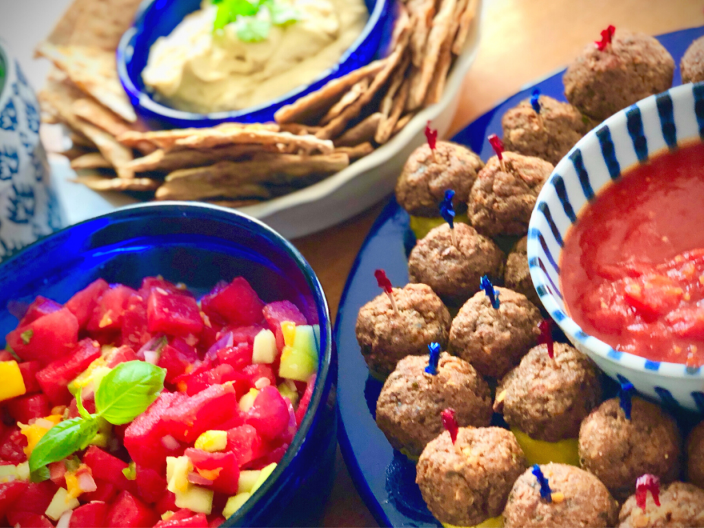 An image of blue bowls with vegan 4th of July foods including vegan meatballs, watermelon salad and hummus with chips.