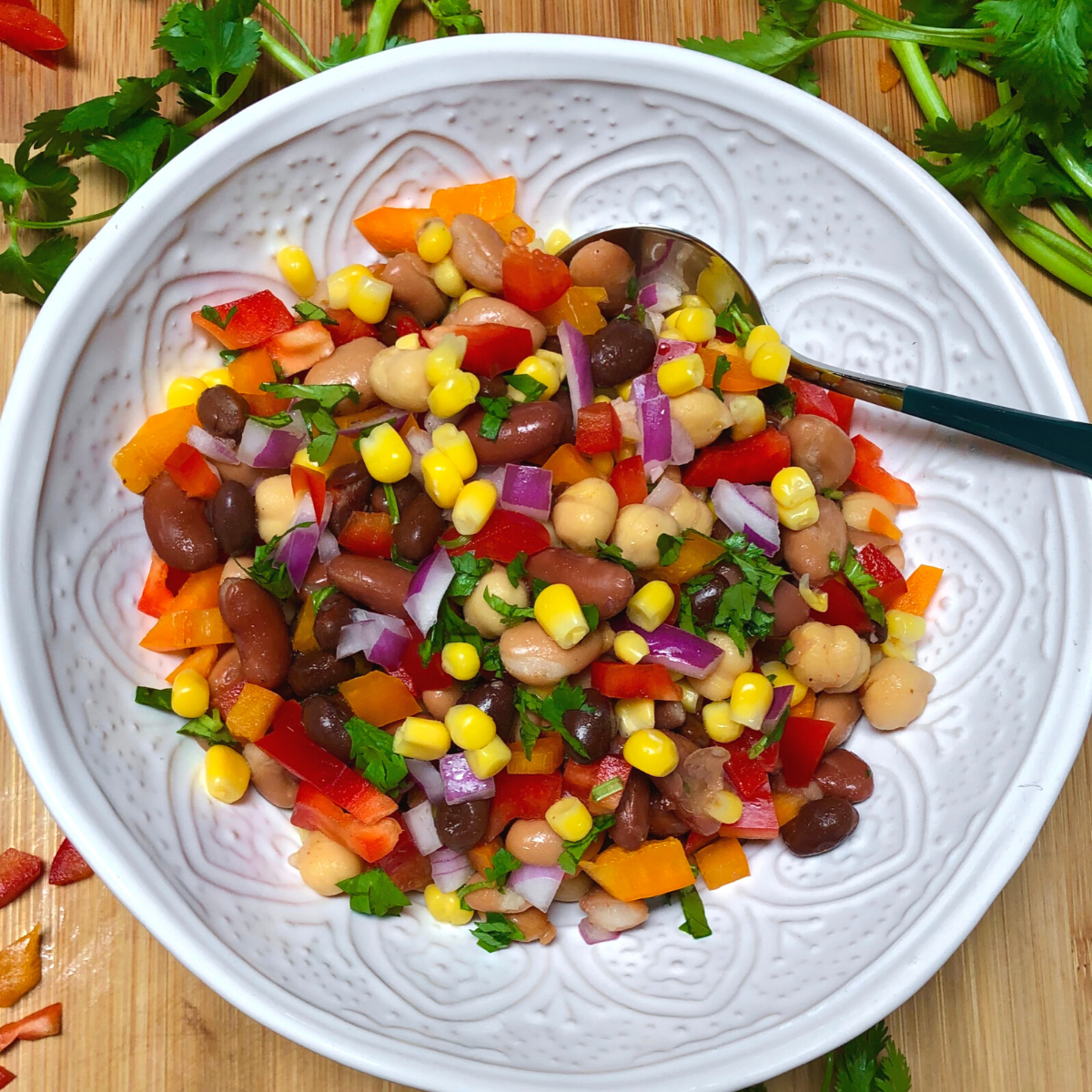 Vegan bean salad with peppers, corn and cilantro in a bowl.
