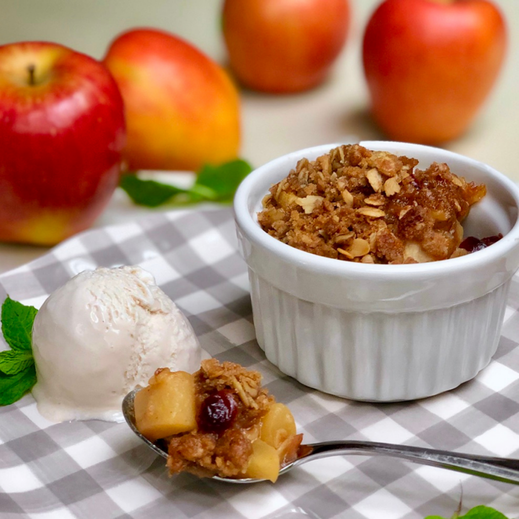 A white ramekin with vegan apple crisp set atop a grey and white checkered plate with a scoop of vegan ice cream. There are red apples in the background.