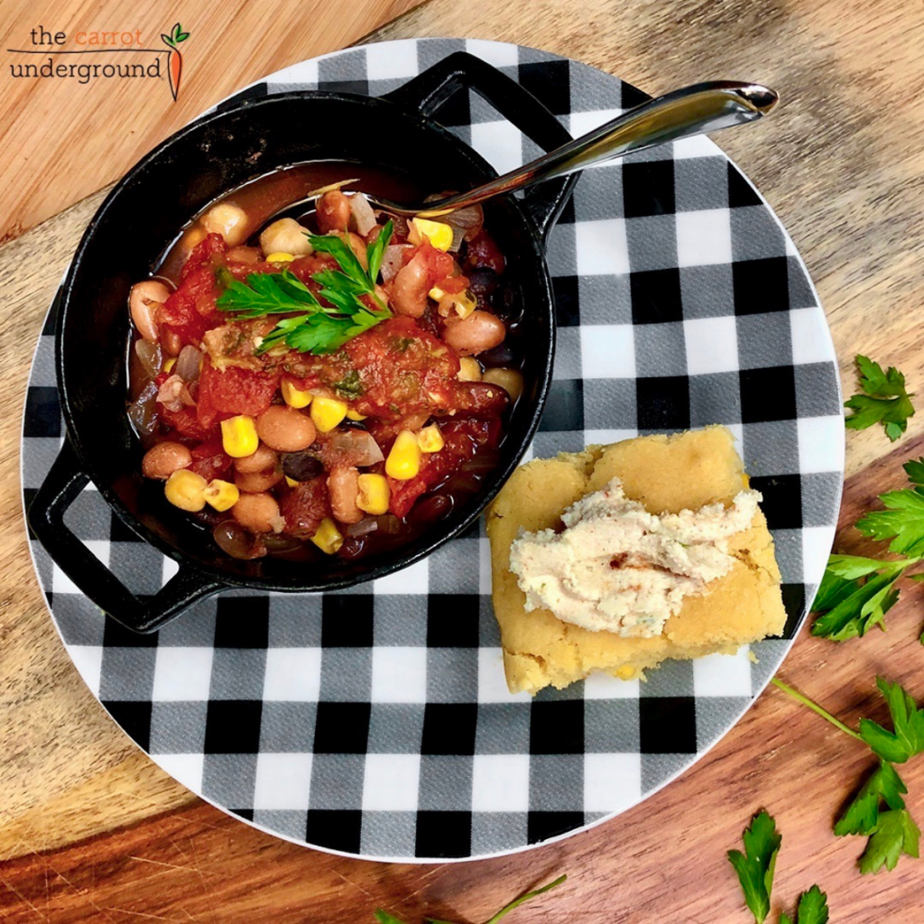 A small black cast iron pot with homemade vegan chili and a black and white checkered plate with a slice of vegan cornbread with non-dairy butter.