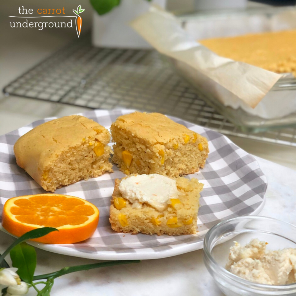 A grey and white gingham ceramic plate with three slices of vegan cornbread and butter and an orange slice.