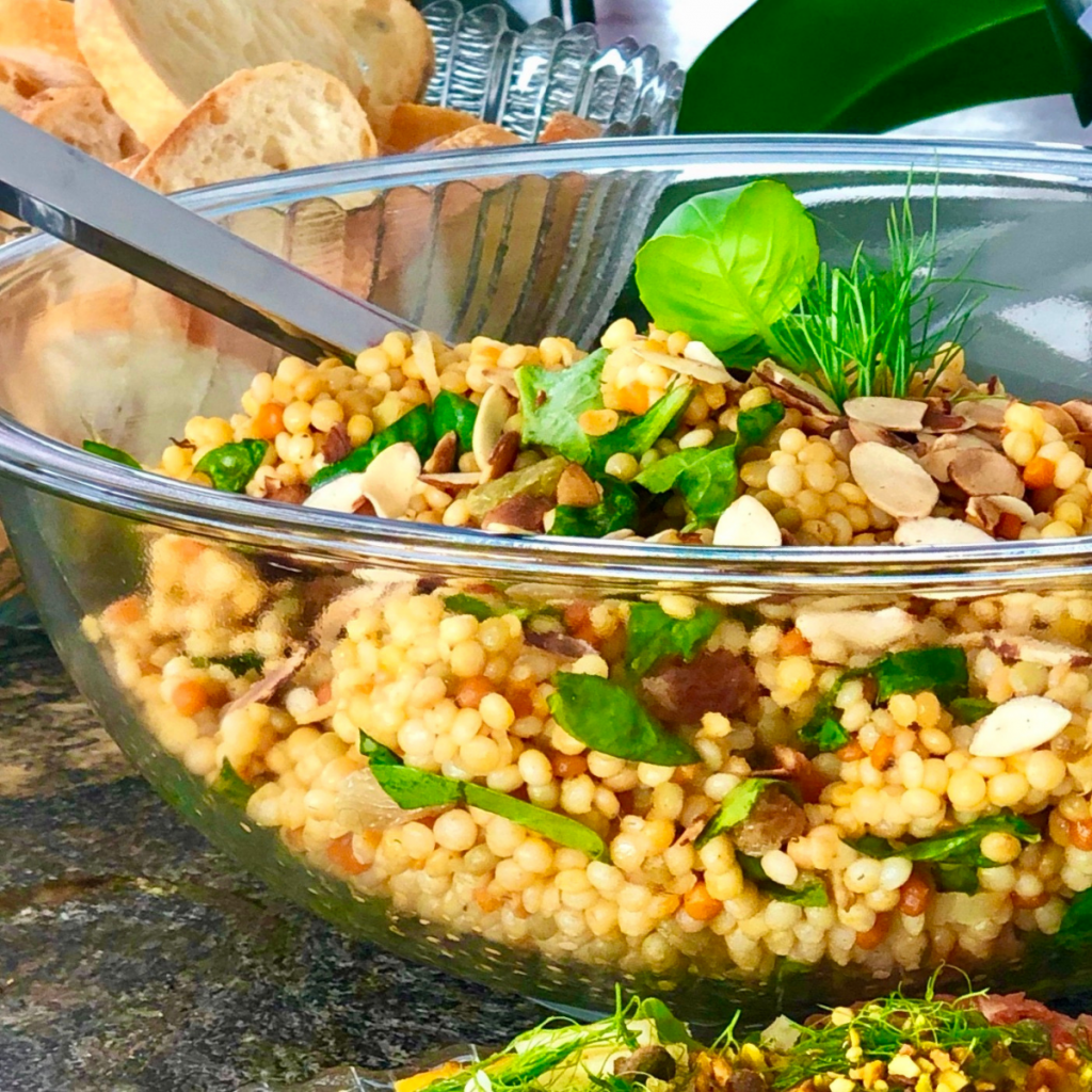 A glass bowl filled with Israeli couscous salad and fresh herbs.