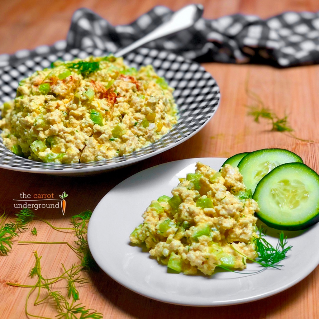Two dishes filled with vegan eggless salad and cucumber slices.