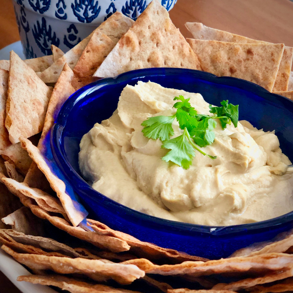 A blue bowl filled with creamy homemade hummus, surrounded by pita chips.