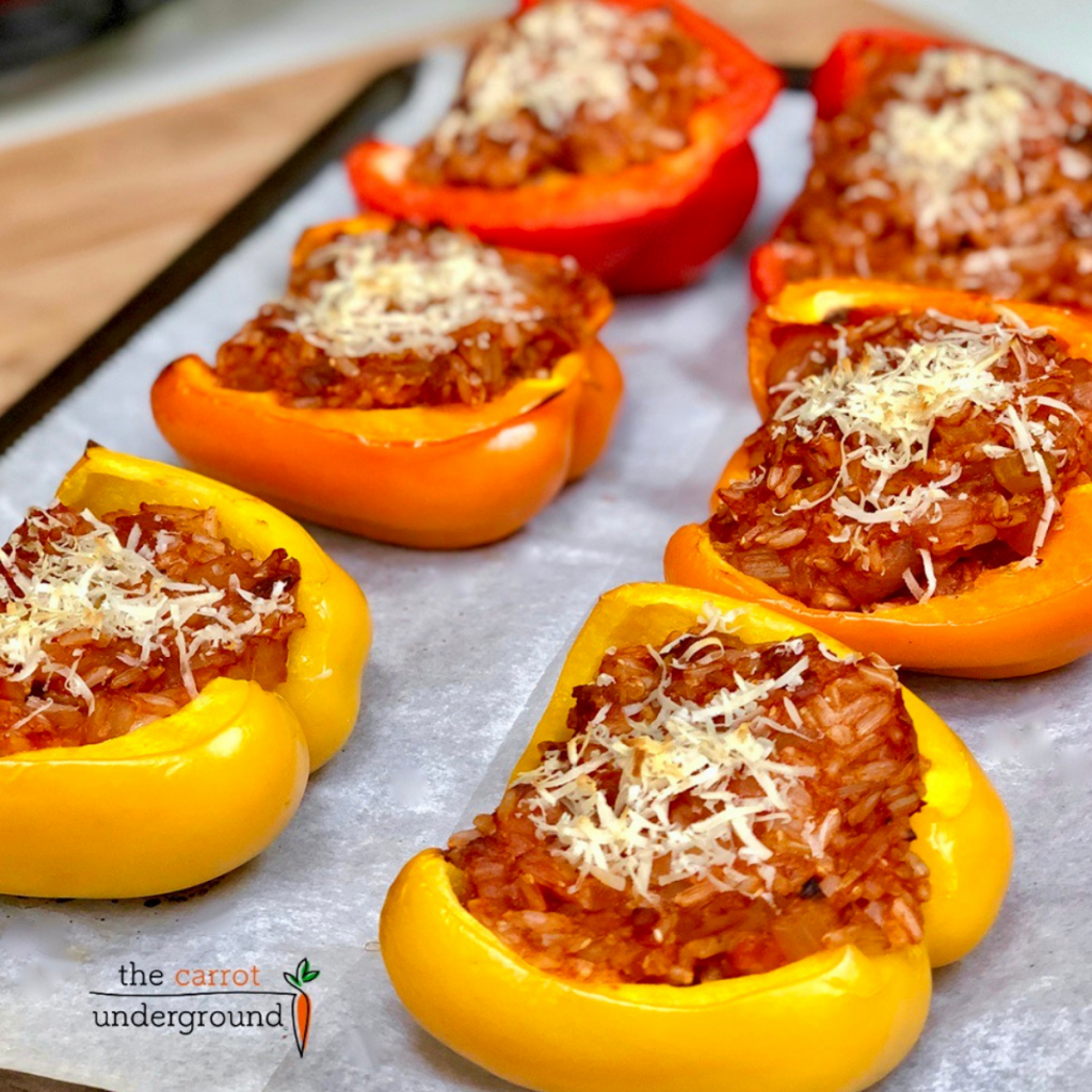 A baking pan with red, orange and yellow vegan stuffed bell peppers.
