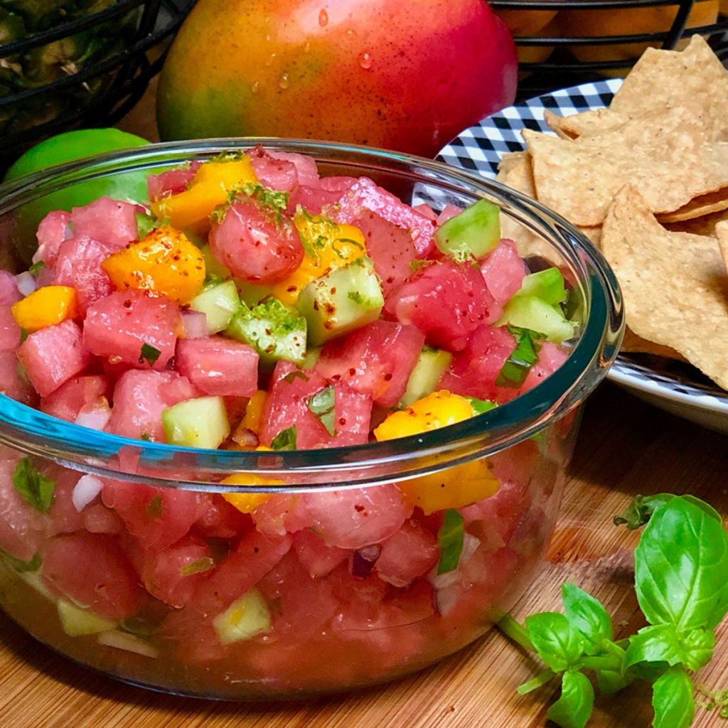 A glass bowl filled with watermelon, mango and cucumber pico de gallo arranged next to a bowl of chips and fresh fruit.