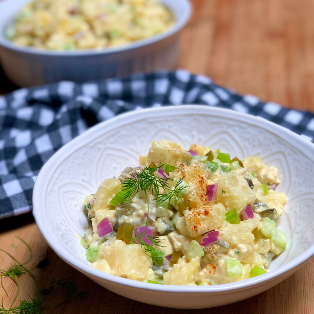 A white bowl filled with vegan old fashioned potato salad.