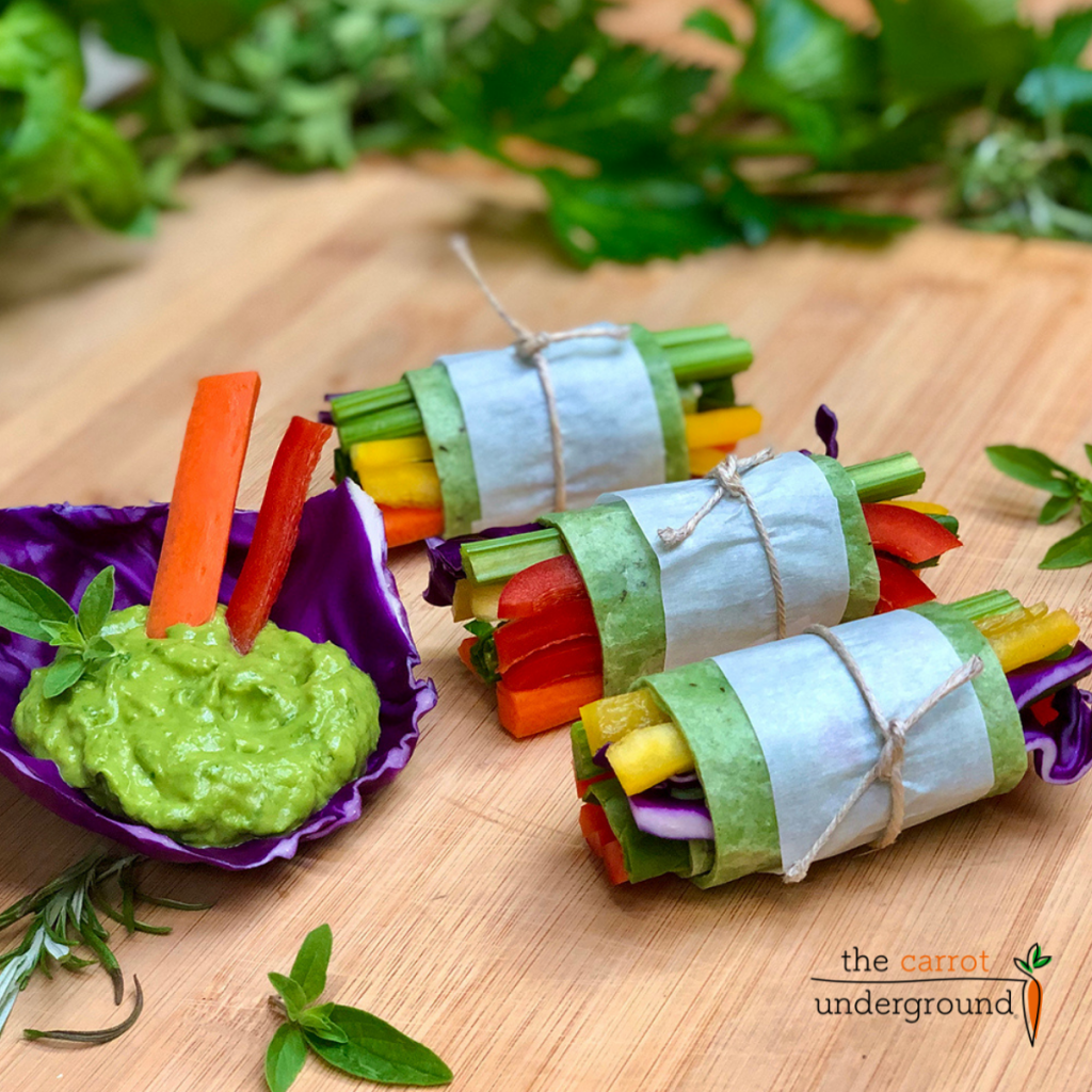Spinach tortillas wrapped around strips of celery, bell pepper, spinach and purple and tied with jute cord. A purple cabbage leaf filled with  avocado basil dressing.