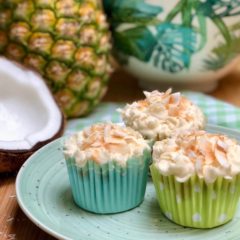 Three pineapple coconut  cupcakes on a plate.