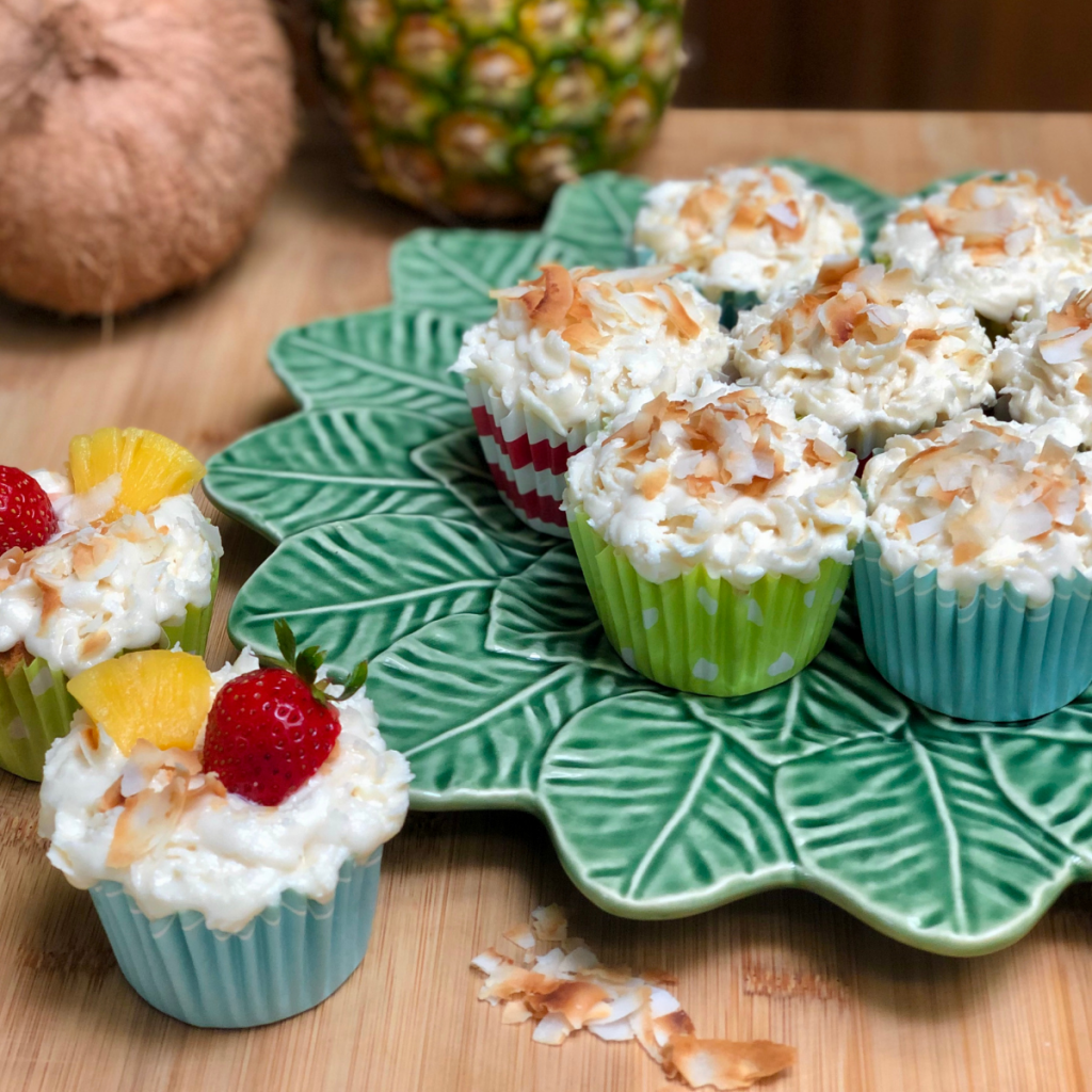 Vegan pina colada cupcakes with coconut buttercream frosting topped with toasted coconuts and fresh fruit.