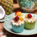 Three vegan pina colada cupcakes arranged on a plate.