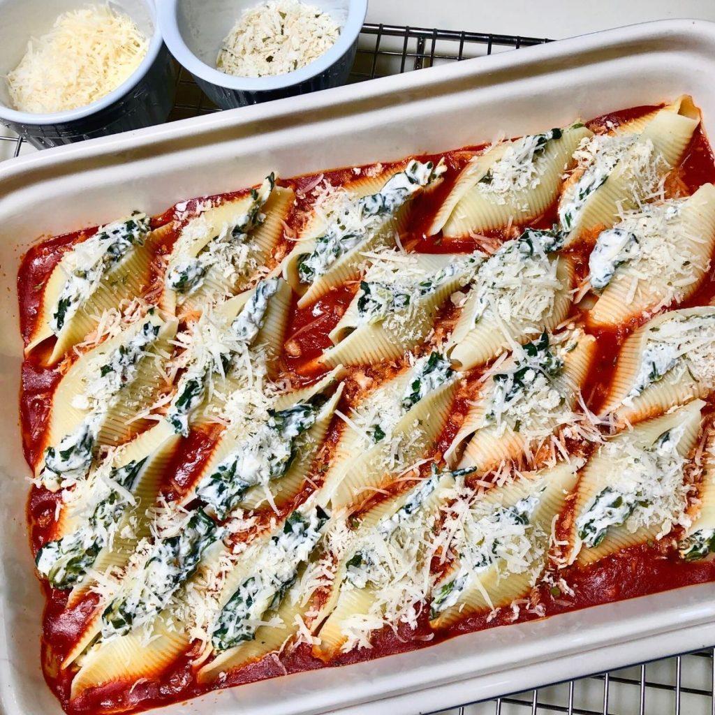 Vegan spinach ricotta stuffed pasta shells in baking dish.