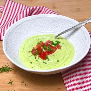 Vegan chilled cucumber avocado soup in a bowl garnished with diced tomato, jalapeno and fresh herbs.
