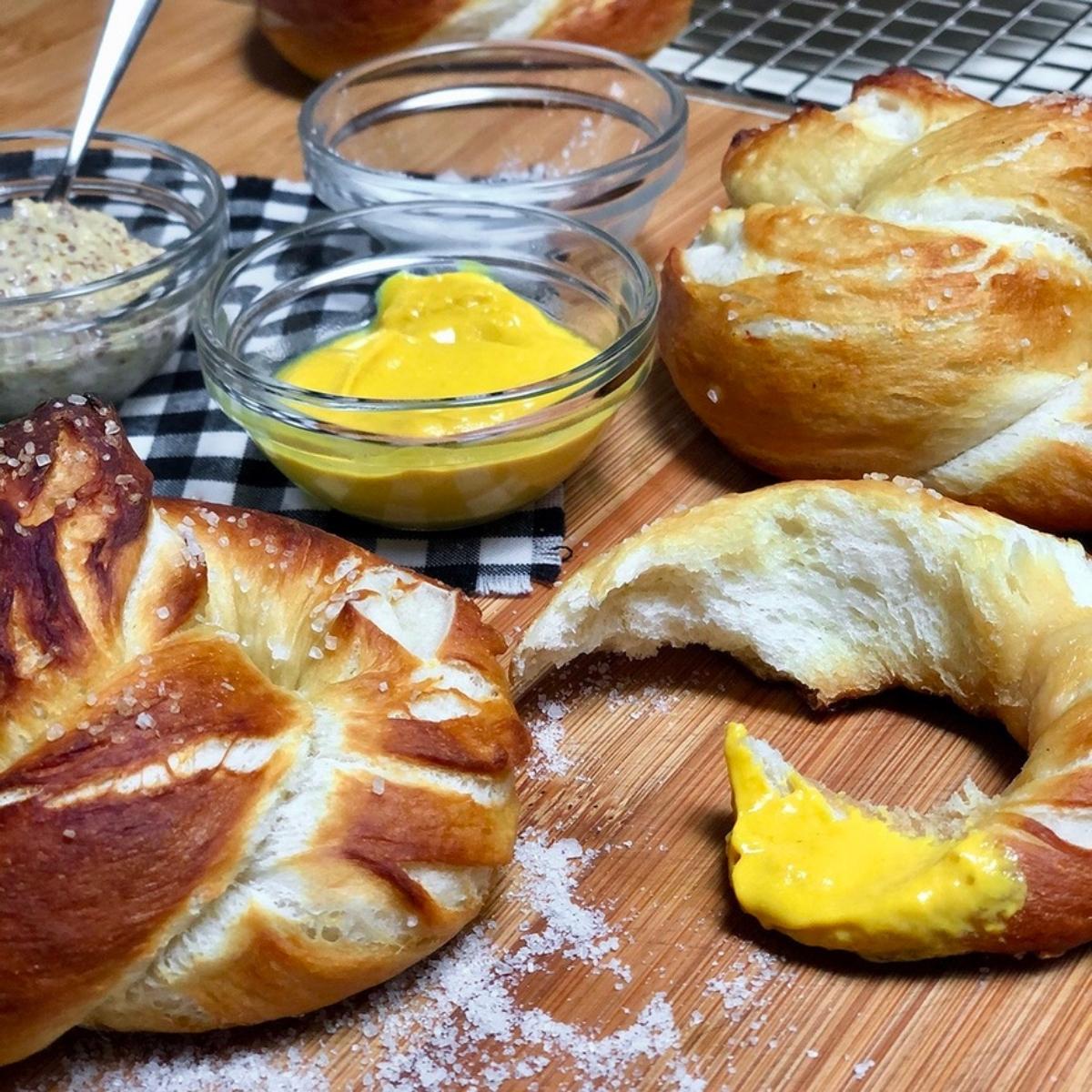 Best Vegan Homemade Soft Pretzels with mustard and salt on a cutting board.