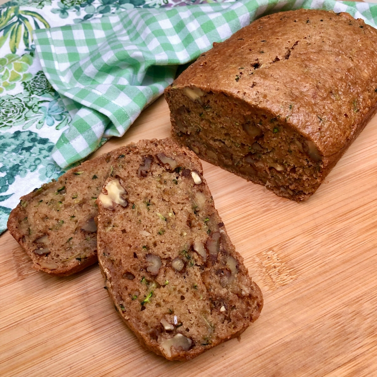 Slices of simple vegan zucchini bread with walnuts on a bamboo board and tea towel.