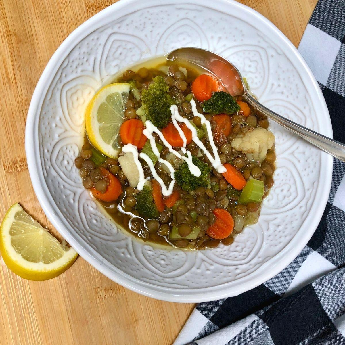 A bowl of easy vegan lentil veggie soup garnished with plain vegan yogurt and lemon wedges.