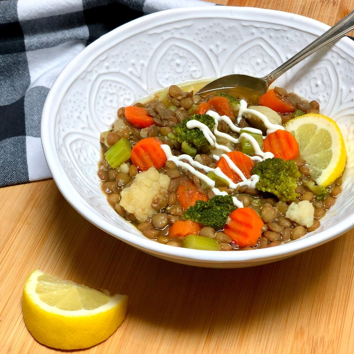 A bowl of easy vegan lentil veggie soup with green lentils, carrots, broccoli, cauliflower and celery, garnished with a drizzle of plain vegan yogurt and lemon wedges.