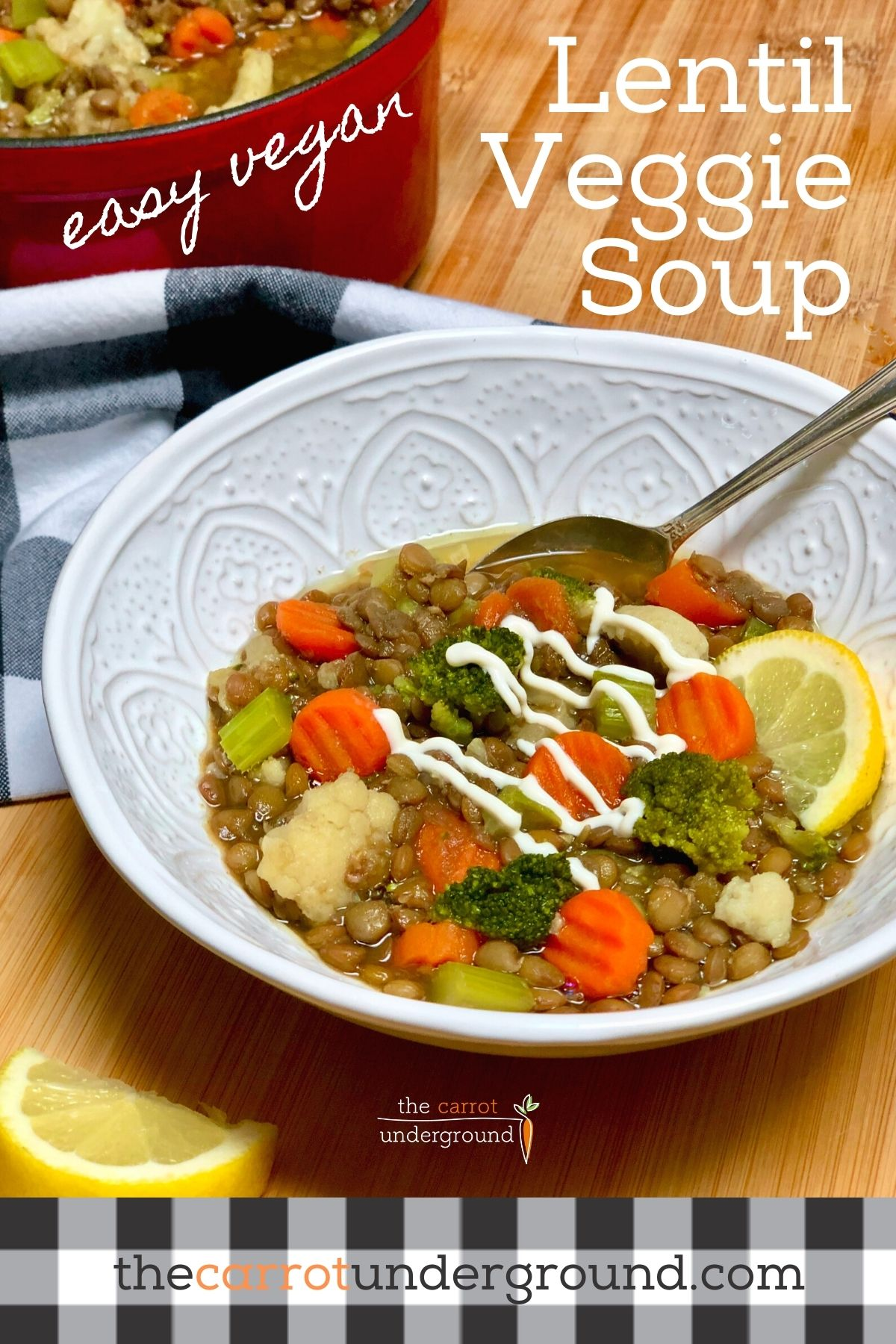 A bowl of easy vegan lentil veggie soup with a drizzle of plain vegan yogurt and lemon wedge.