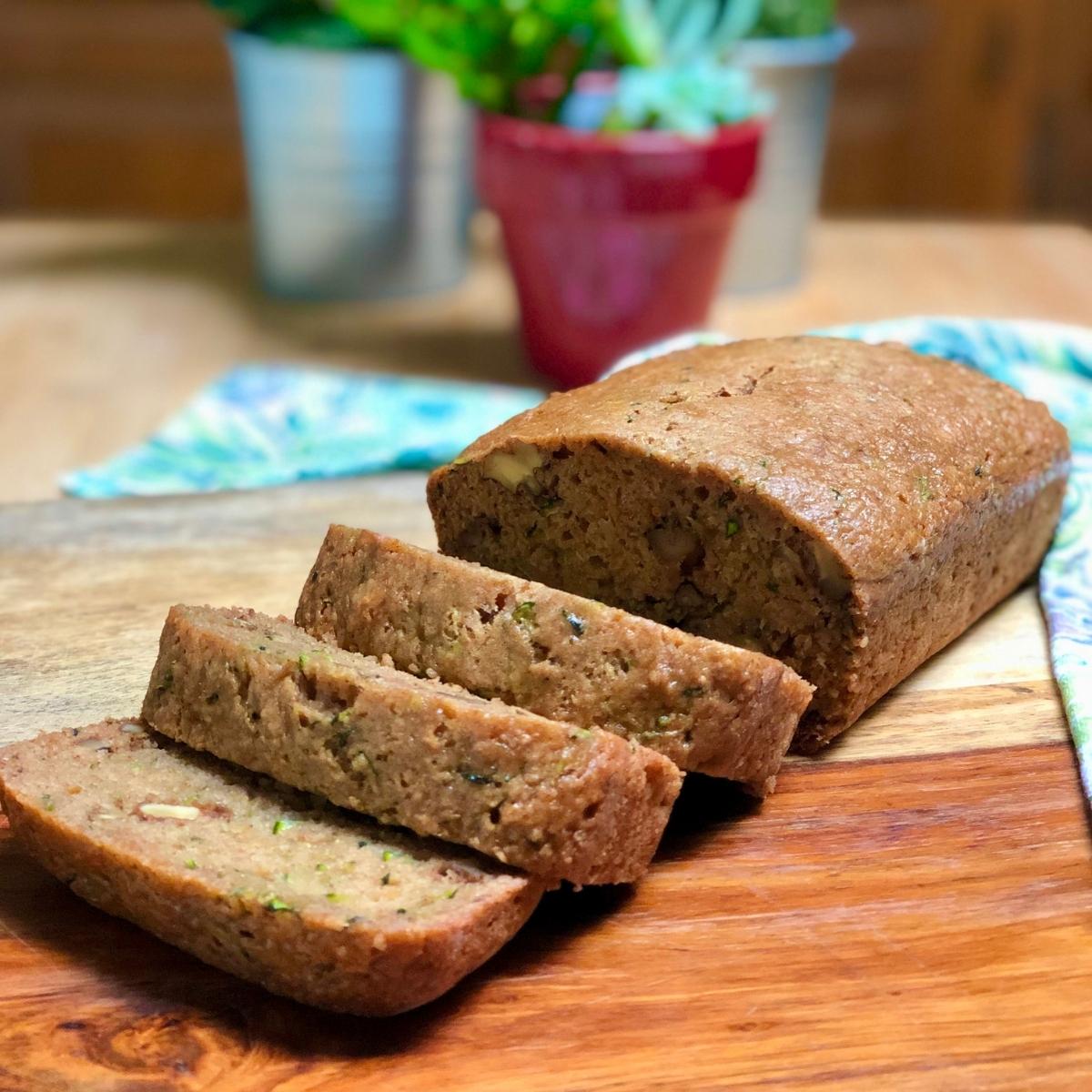 A sliced loaf of simple vegan zucchini bread on a wood cutting board.