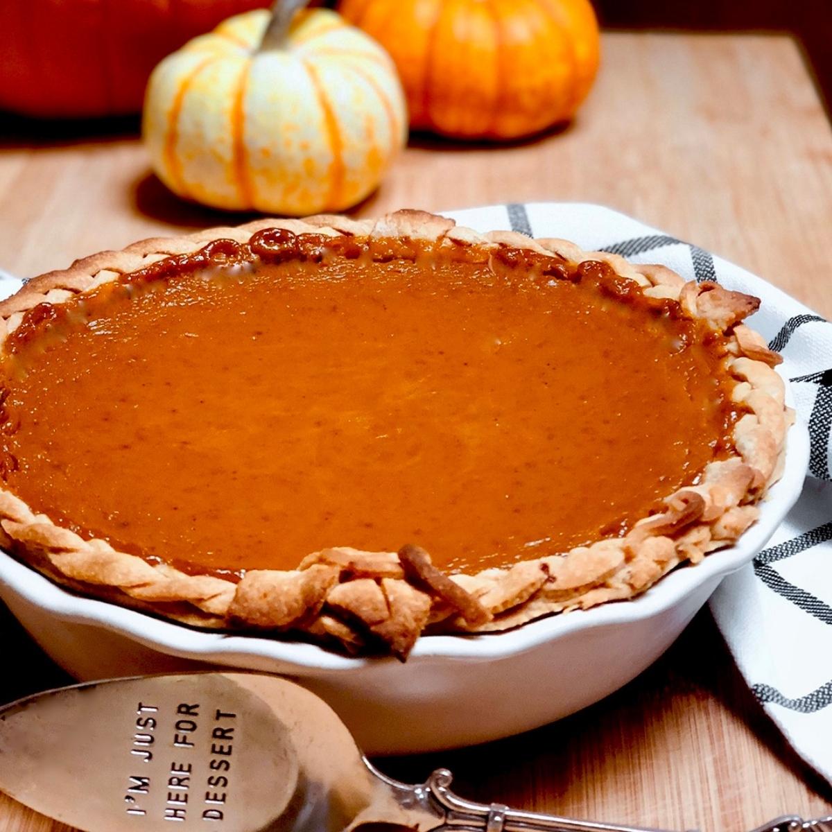 A homemade vegan pumpkin pie on a cutting board.