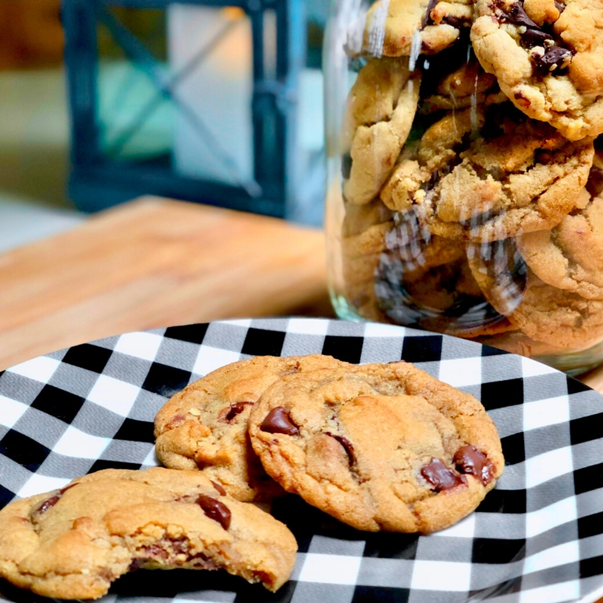 A checkered plate with vegan chocolate chip cookies next to a glass jar filled with cookies.