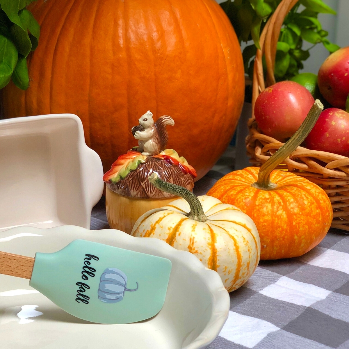 Pumpkins, apples and bakeware in a fall-themed display.