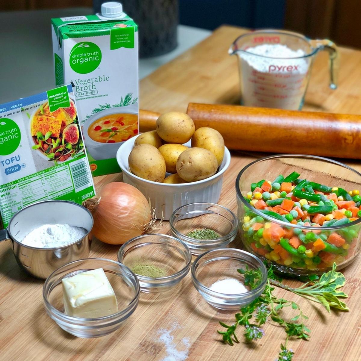 Ingredients for preparing homemade vegan pot pie with tofu, including tofu, vegetable broth, potatoes, onion, mixed veggies, butter, flour and seasonings.