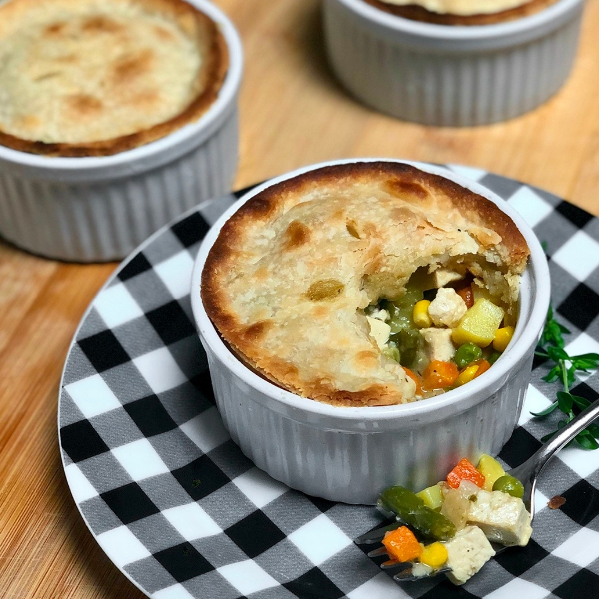 Homemade vegan pot pie with tofu baked inside a white ramekin atop a black and white gingham print plate.