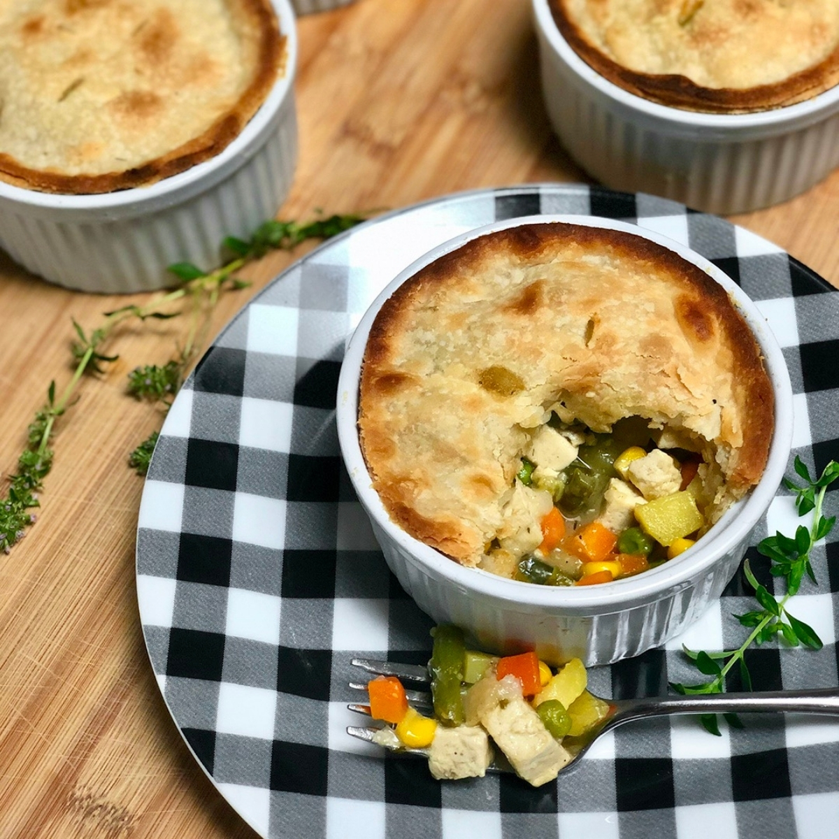 Homemade vegan pot pie with tofu baked inside a white ceramic ramekin and placed on a black and white checkered plate.