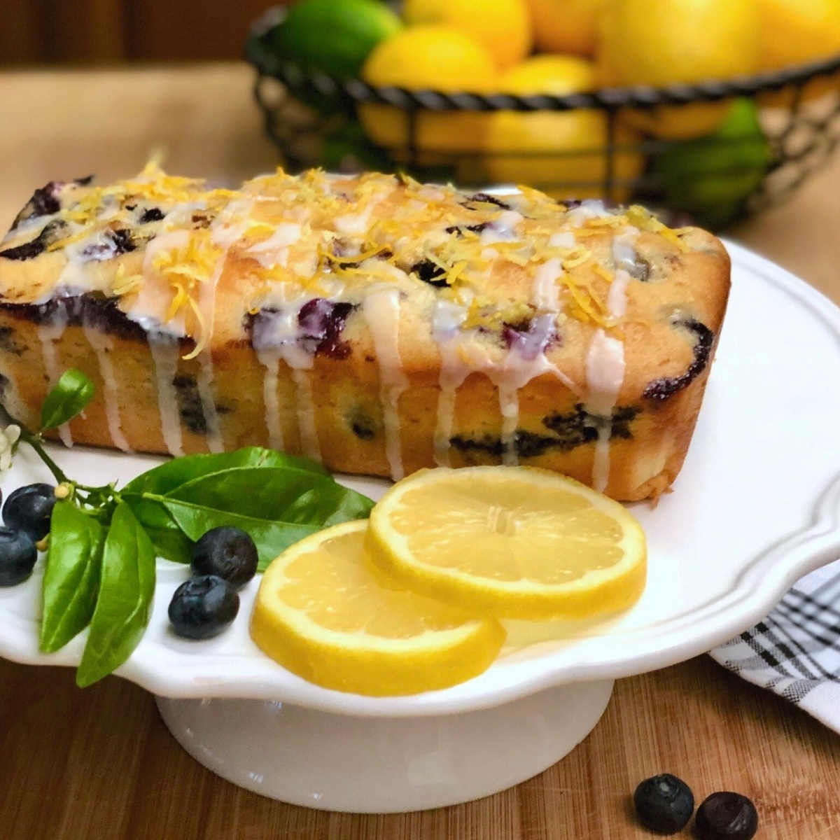 A loaf of vegan lemon blueberry bread drizzled with icing and topped with grated lemon zest.