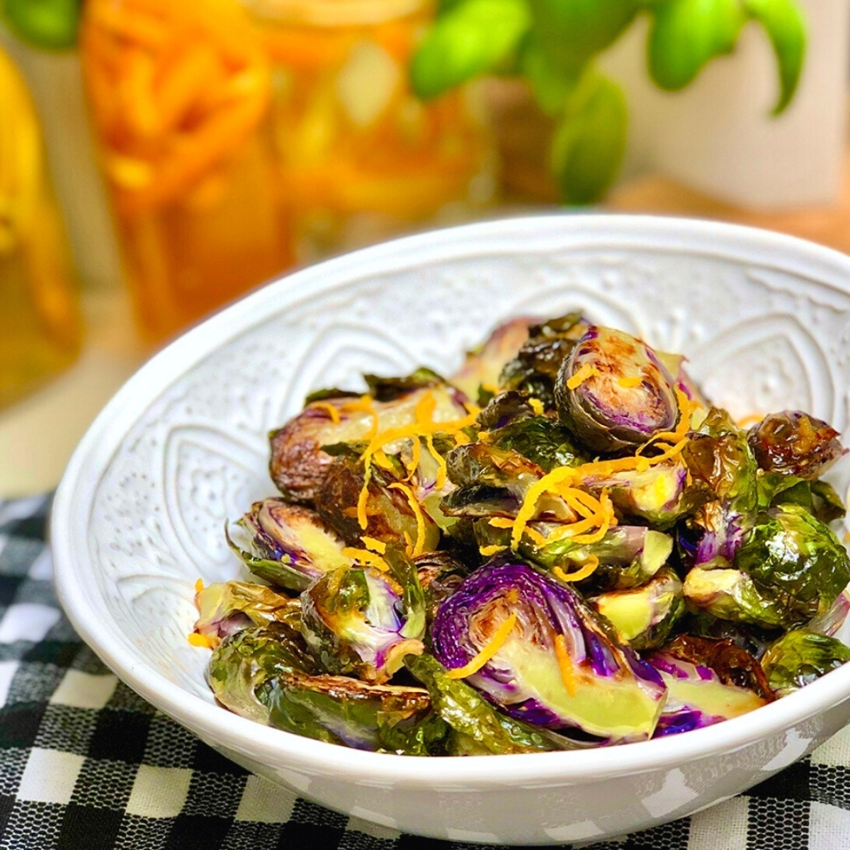 A white dish with vegan orange balsamic roasted Brussels sprouts.
