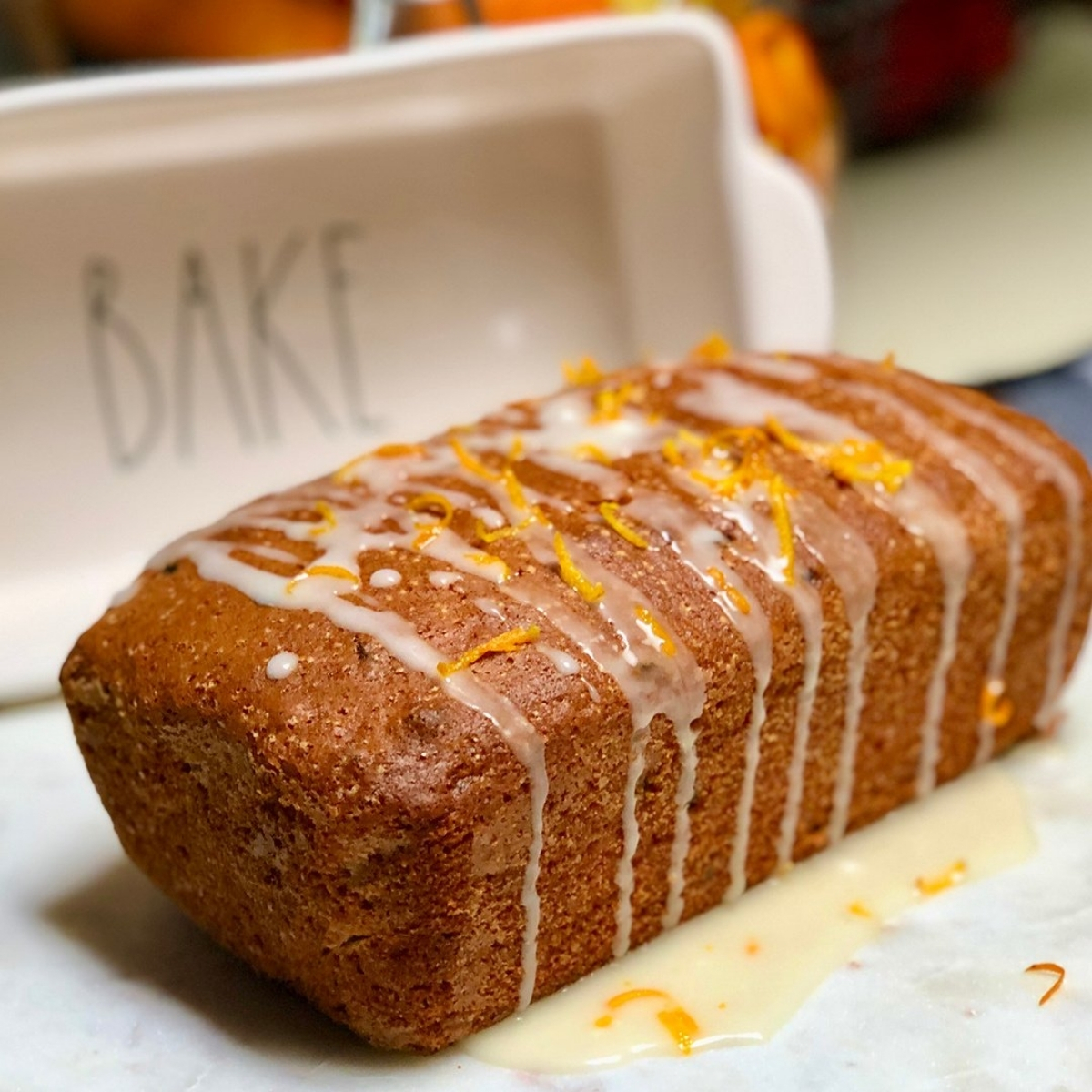 A loaf of vegan orange cranberry bread drizzled with lemon icing and topped with orange zest.