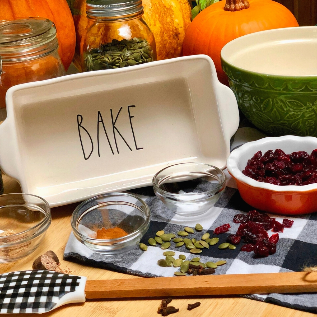 A fall-inspired display of bakeware, dried cranberries and spices.