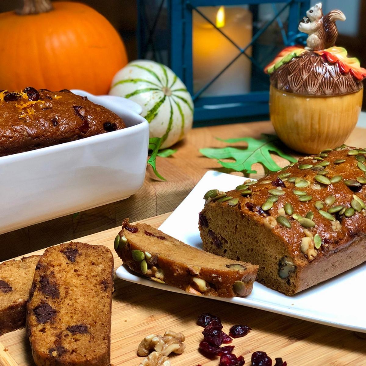 Loaves of vegan pumpkin bread arranged in a fall-themed setting.